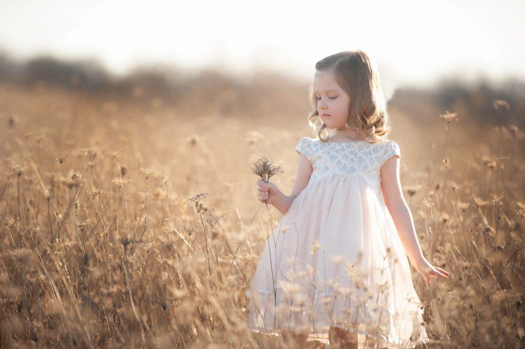 little girl in dress in field